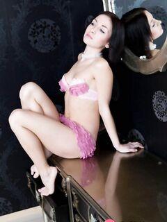 Горячая брюнетка позирует на стуле и манит своей волосатой киской - фото