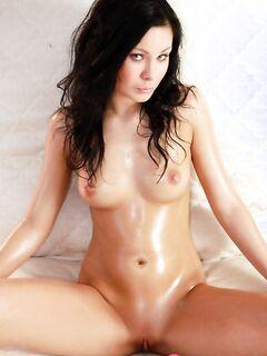 Голая девушка в масле сексуально позирует и светит бритой писькой на фото - фото