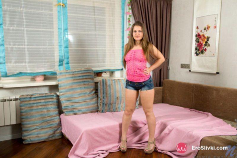 Обаятельная девушка ласкает гладенькую киску рукой на кровати - фото