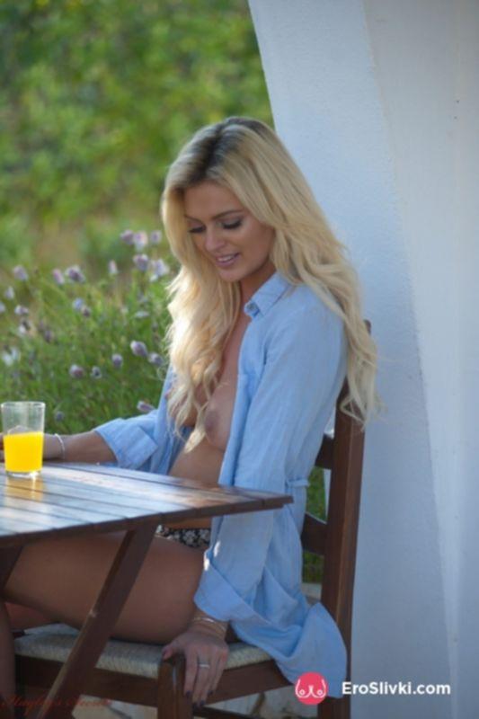 Белокурая красотка с обнаженной грудью на лоне природе решила выпить соку - фото