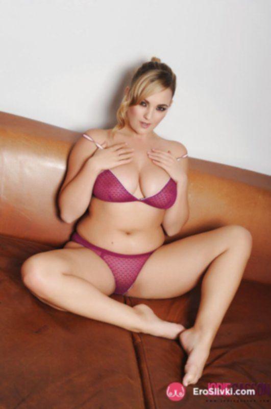 Фигуристая блондинка эротично позирует в нижнем белье на кожаном диване - фото