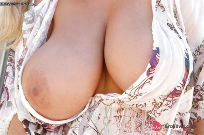 Эффектная дамочка с огромными сиськами эротично позирует во дворе - фото
