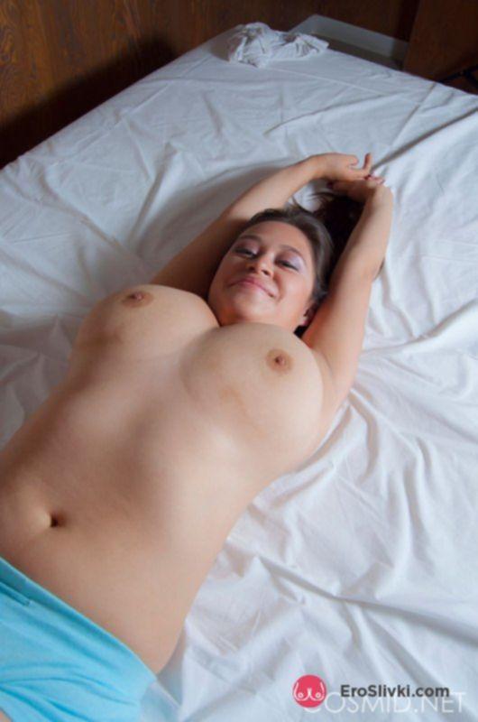 Шатенка с большими сиськами нежно ласкает клитор в своей постели - фото