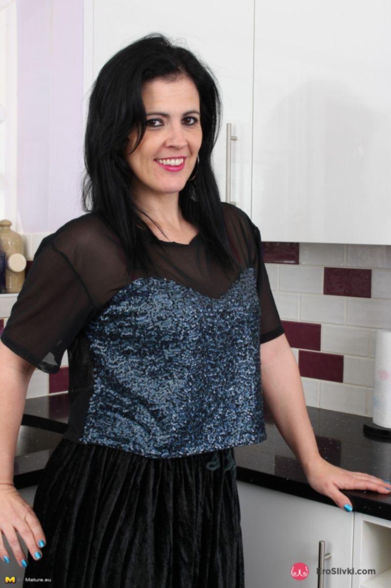 Темноволосая домохозяйка с большой задницей оголяет шикарные дойки на кухне - фото