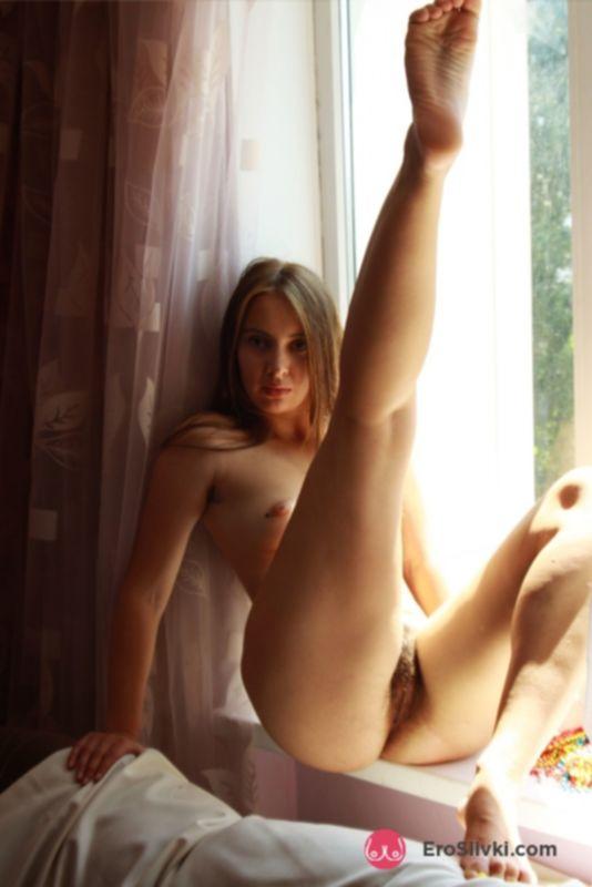Кудесница Аля с миниатюрной грудкой раздвигает ножки и показывает волосатую писю у окна - фото