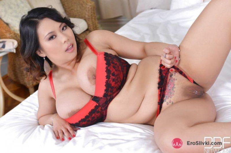 Полноватая азиатка играет со своей выбритой вагиной на кровати - фото