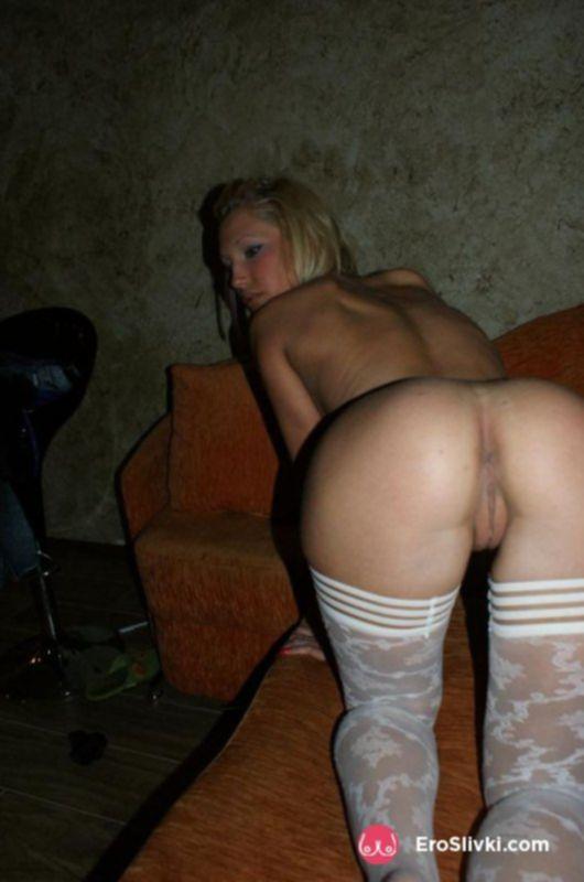 Сексуальная блондинка в белых чулках позирует голой на диване - фото