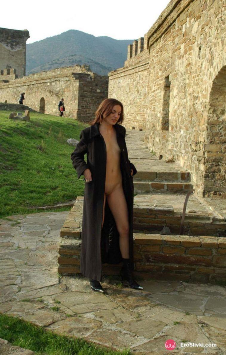 Худощавая шатенка в пальто на голое тело прогуливается по улице - фото
