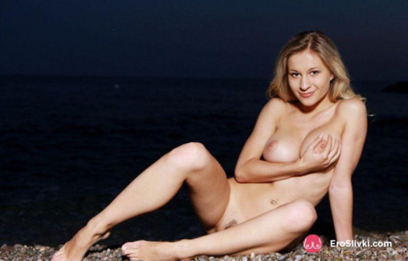 Грудастая блондиночка эротично позирует на морском пляже - фото