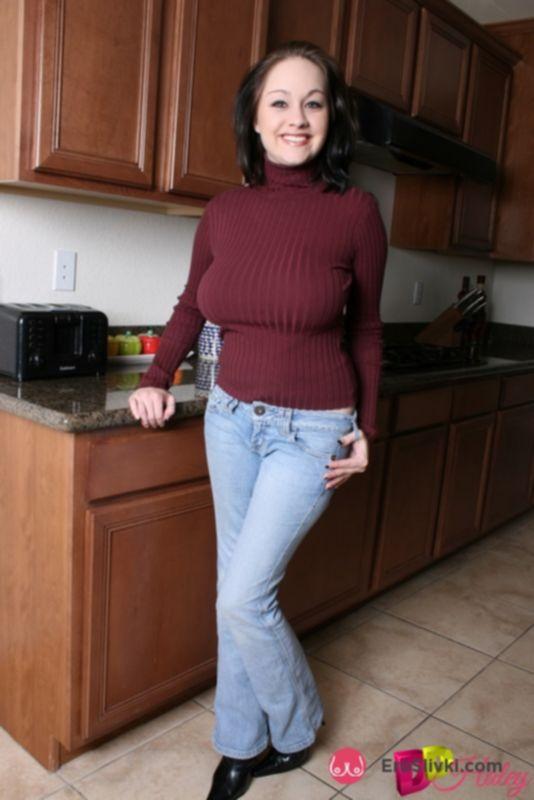 Домашняя модель с лучезарной улыбкой показывает на кухне объемные сиськи и тату на копчике - фото